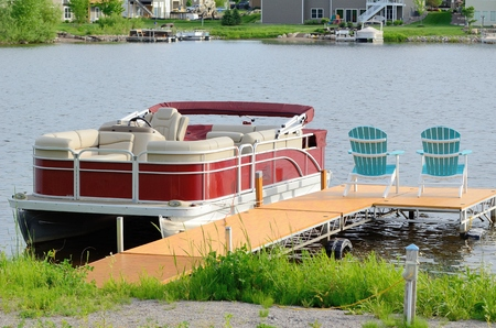 adirondack: Red Pontoon Boat Tied to a Dock With Two Chairs