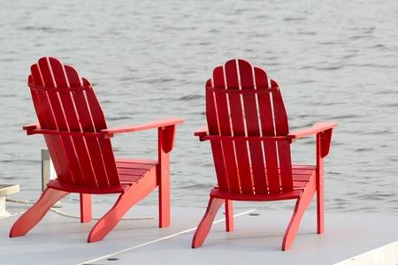 湖のほとりにドックの 2 つの赤 Adirondack の椅子