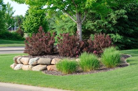 Landscaping met Weigela struiken en Rock keermuur bij een woonhuis
