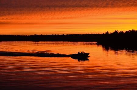 穏やかな湖の日没後モータリング ボート