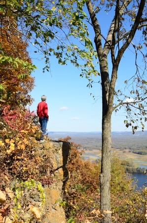 秋にミシシッピ川の渓谷上の崖に立っている男 写真素材