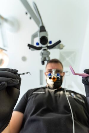Dentist with magnifying glasses looking from above