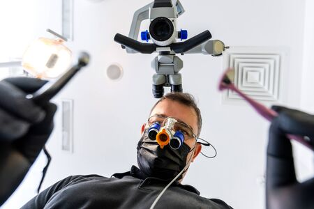 Dentist with magnifying glasses doing oral examination