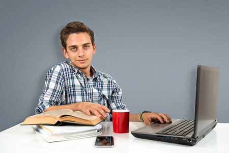 Young man studying with book and laptop