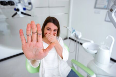 Woman experiencing fear of dentist is showing stop sign with her hand Imagens
