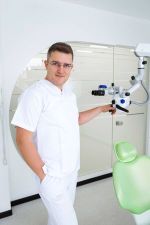 The dentist is standing with a microscope Imagens