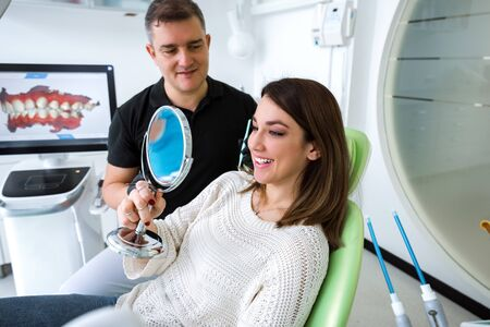 Young woman looking in the mirror after a dental treatment Imagens