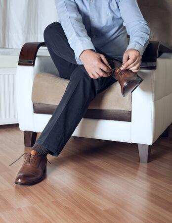 Man ties his brown shoes