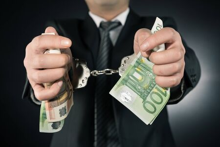 Businessman is arrested and handcuffed with Euro Stock Photo