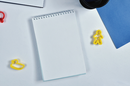 White Notebook, blue paper, pen and pencil case, yellow plastic duck toy and person toy on white paper background Standard-Bild
