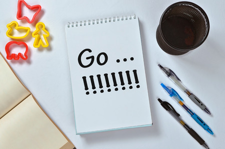 Go...!!!!!! text on notepad with office accessories. Business motivation, inspiration concepts, pen and pencil case, yellow plastic duck toy and person toy, red butterfly toy and red elephant toy on white paper background