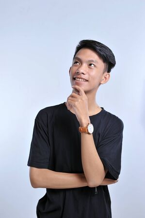 Handsome young asian boy wearing black t-shirt and wristwatch with hand on chin thinking about question, pensive expression. Smiling with thoughtful face. Doubt concept. Over the white background