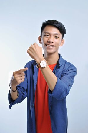 Potrait of handsome young asian man pointing to the wristwatch with pretty smiling isolated on grey background