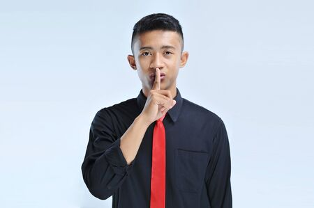 Young asian business man asking to be quiet with finger on lips. Silence and secret concept over isolated background