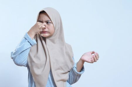 Close-up portrait of young asian woman holding nose closed because of bad smell islolated grey background Imagens