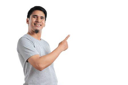 Knap van gelukkig lachende Aziatische man wijzend van een copyspace geïsoleerd op een witte achtergrond