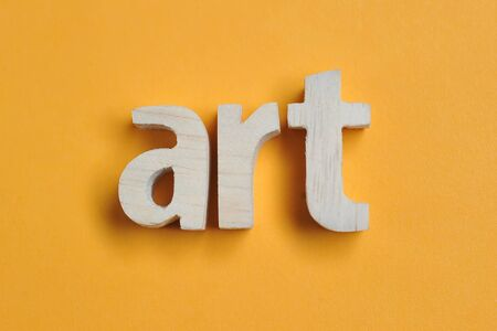 Word ART carved from wood. Art text on yellow backdrop for your desing, concept.