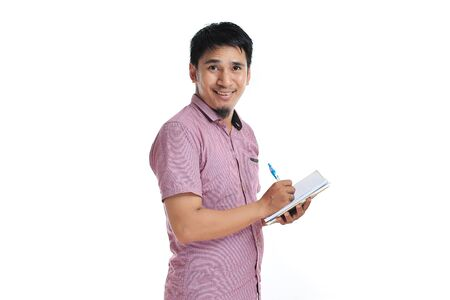 Asian male writing on his diary with pink t-shirt isolated on white background