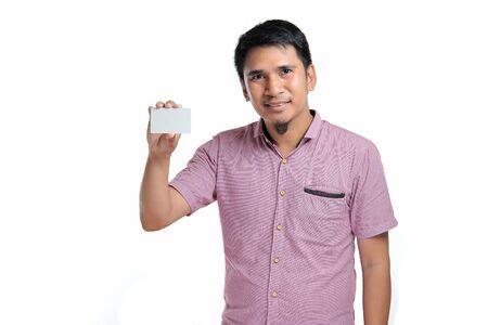 Retrato de hombre asiático sonriente sosteniendo una tarjeta de presentación en blanco sobre fondo blanco.