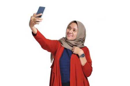 Happy beautiful asian woman smiling wearing hijab doing self phone or selfie on a white background