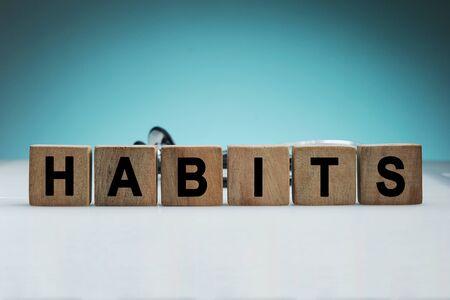 Was sind deine Gewohnheiten? Schild mit dem Wort Gewohnheiten auf weißem Schreibtisch in blauem Hintergrund blue Standard-Bild