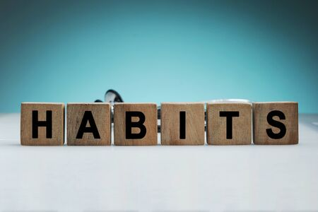 What is your habits? Sign with the word habits on white desk in a blue backgroud Stok Fotoğraf
