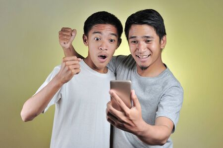 Portrait two young Asian men surprised, two young Asian men looking at cellphones screen. Amazed millennial guy received mail with unexpected news, big sale discount, good deal or offer, isolated on yellow studio background