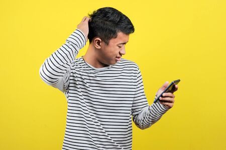 Portrait of confused man looking at smartphone