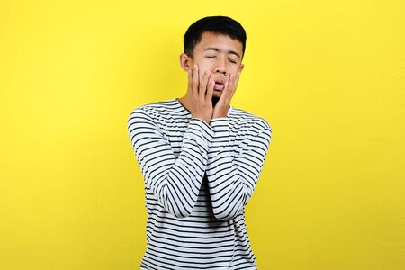 Confused man doing foolish gesture, disappointed expression, isolated on yellow background Stok Fotoğraf