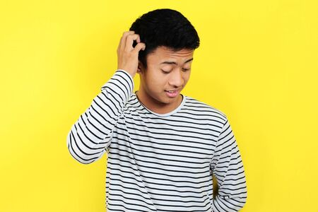 Portrait of confused man, isolated on yellow background