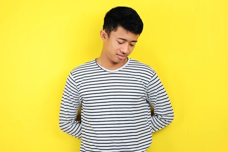 Young Asian man doing annoyed gesture isolated on yellow background