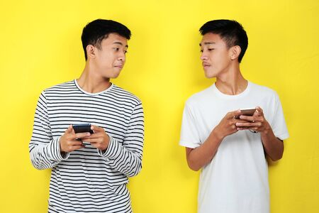 Portrait of  funny two young Asian men looking to each other's cellphones, isolated on yellow background Stock fotó