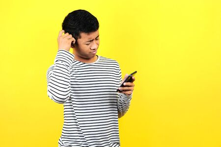 Portrait of confused man looking at smartphone, isolated on yellow background Stock Photo