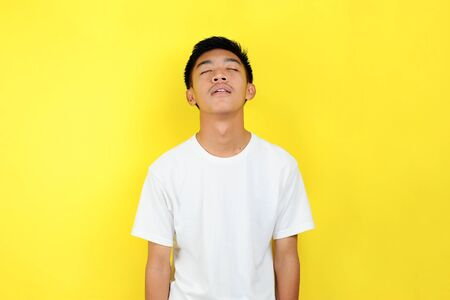 Young asian man was dumbfounded looking up, his mouth open, silent expectation of observation shocked by what he saw, isolated on yellow background Stock fotó