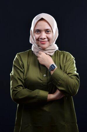 Feliz de joven musulmana vistiendo hijab sonriendo sobre fondo negro