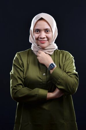 Happy of young muslim woman wearing hijab smiling on black background Foto de archivo