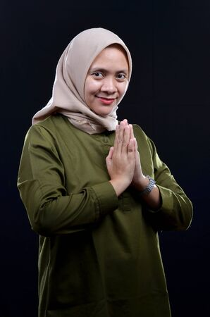 Feliz de joven musulmana vistiendo hijab sonriendo sobre fondo negro Foto de archivo