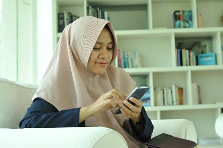 Portrait of cheerful smiling muslim woman girl using smartphone at living room.