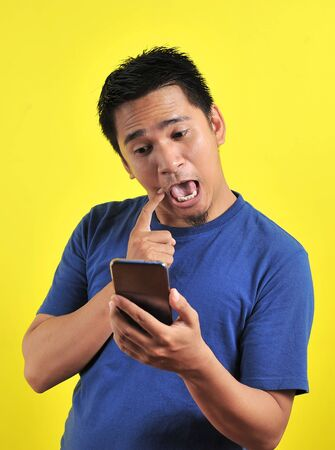 Funny Asian man using cellphone, isolated on yellow background Stockfoto