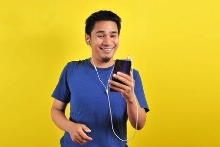 Asian man in casual blue t-shirt happy wearing headset listening to music from smartphone, isolated on yellow background. Reklamní fotografie