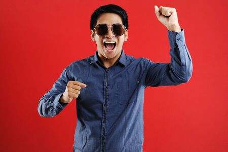 Young asian man happy and excited expressing winning gesture. Successful and celebrating on red background