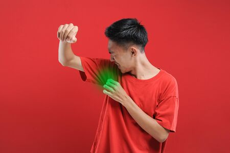Asian man with hyperhidrosis sweating under armpit, feel bad with body, odor smell problem, isolate on red background