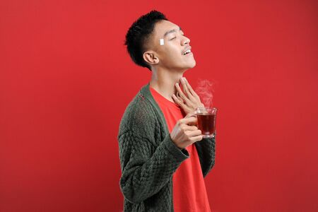 Sick cold and headache, Happy of Young Asian man wearing a sweater while drinking hot tea, isolated on red background