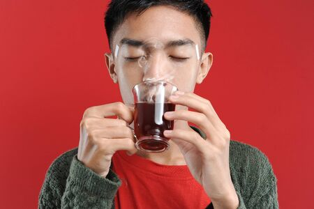 Sick cold and headache Young Asian man wearing a sweater while drinking hot tea, isolated on red background Stok Fotoğraf