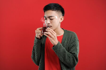 Sick cold and headache Young Asian man wearing a sweater while drinking hot tea, isolated on red background