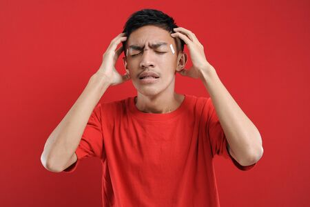 Young Asian man suffering from vertigo headache, A studio portrait of a painful Asian youth, holding his head. on red color