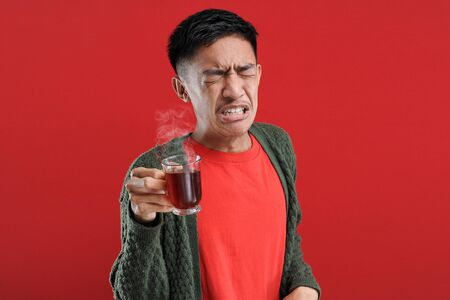 Young Asian man drinking a cup of bad tea / bitter tea standing over isolated red background