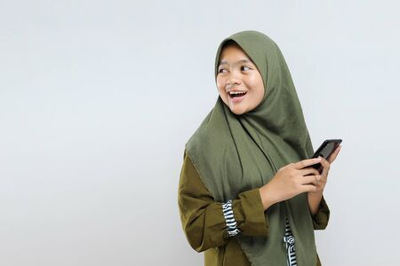 Happy young Asian Muslim woman smiling holding smartphone look at copy space, isolated on gray Reklamní fotografie