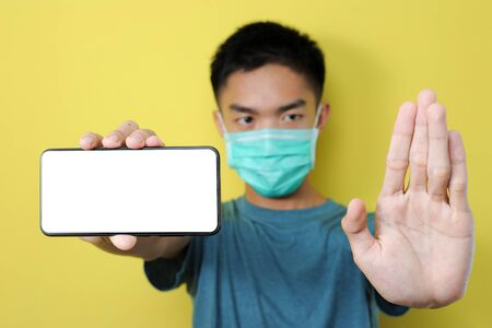 Young Asian man wearing protect mask doing stop gesture to stop share hoax, fake news, Isolated on yellow