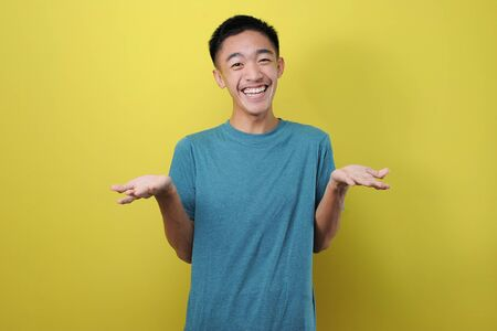 Portrait of relaxed smile young Asian man stay calm down, isolated on yellow